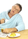 Nerdy Man Asleep. Nerdy middle aged man falls asleep at the breakfast table with a cup of tea and muffins Stock Photography