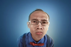 Nerdy man confused expresion. Nerdy man confused expression, wearing glasses, bow and tie, blue background Royalty Free Stock Photos