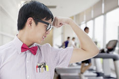 Nerdy Man With Glasses Flexing His Bicep in the Gym Royalty Free Stock Image