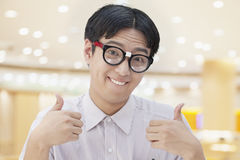Nerdy Man with Glasses Giving Thumbs Up, Looking At Camera Stock Photo