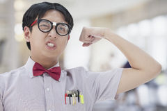 Nerdy Man with Glasses Making A Face and Flexing His Bicep Stock Image