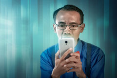 Nerdy man holding cellphone Stock Images