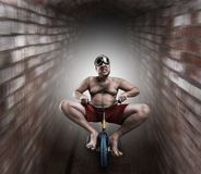 Nerdy man riding a small bicycle Royalty Free Stock Photos