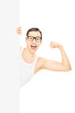 Nerdy man showing biceps behind blank panel Royalty Free Stock Image