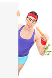 Nerdy man in sportswear eating carrot behind panel Stock Images