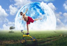 Nerdy man standing on a small bicycle Royalty Free Stock Photography