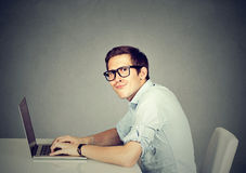Nerdy man using a laptop computer Royalty Free Stock Images