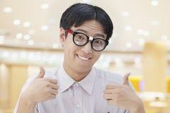Nerdy Mann mit den Gläsern, die Daumen, Kamera betrachtend aufgeben Stockfoto