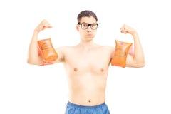 Nerdy młody człowiek z pływackimi ręka zespołami pokazuje jego mięśnie Fotografia Royalty Free