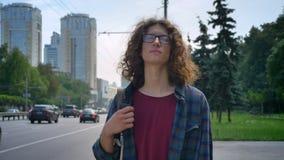 Nerdy stilig man i exponeringsglas med lockigt hår som kontrollerar på telefonen och väntande på taxi, hållande smartphone i hand lager videofilmer
