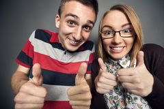 Nerdy teen couple. Happy nerdy teen couple showing ok royalty free stock photos