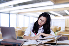 Nerdy teenage girl studying with textbooks Royalty Free Stock Images