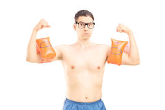 Nerdy ung man med simningarmmusikband som visar hans muskler Royaltyfri Fotografi