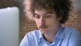 Nerdy ung programmerare med maskinskrivning för mustasch som och för lockigt hår arbetar på bärbara datorn, allvarligt och koncen stock video