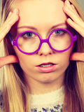 Nerdy woman in big holding head Stock Images