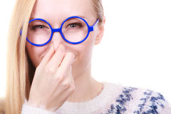 Nerdy woman holding nose smelling bad scent Stock Images
