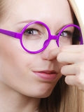 Nerdy woman holding nose smelling bad scent Stock Image