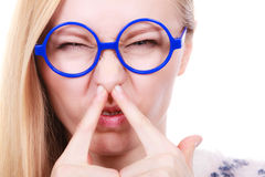Nerdy woman holding nose smelling bad scent Royalty Free Stock Photography