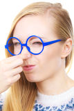 Nerdy woman holding nose smelling bad scent Royalty Free Stock Images