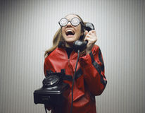 Nerdy woman speaking on a black rotary vintage phone Royalty Free Stock Photos