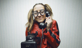 Nerdy woman speaking on a black rotary vintage phone Stock Photography