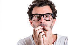 A nerdy young guy apprehensive and scared about something Royalty Free Stock Photo
