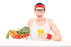 Nerdy young guy holding a glass of orange juice royalty free stock photo