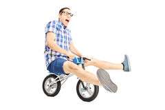 Nerdy young male riding a small bicycle Stock Images