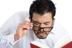 Nerdy young man trying to read the book through his glasses, but having difficulties in doing so Royalty Free Stock Photos