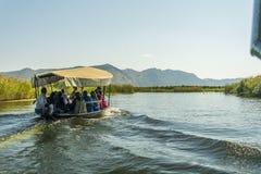 NERETVA,克罗地亚, 2017年9月30日:与游人的小船徒步旅行队neretva河三角洲的,在橘树和橙树之间 免版税库存照片