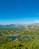 Neretva valley with small lakes and clear blue sky. Green Neretva valley with many crop fields, small lakes and blue sky on upper side Stock Photos