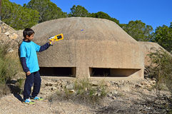 Firing A Nerf Gun. A boy firing a bullet from a toy gun outside a war bunker Stock Photos