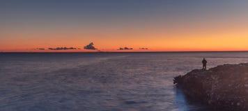 Fisherman on the coast. Nerja, Malaga, Andalusi, Spain - January 21, 2019: A lone fisherman on the coast, with twilight on a sunset of reddish horizon stock photos