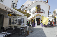 NERJA. MALAGA, SPAIN - APRIL 17, 2013:  People strolling along the pedestrian area full by entertainment facilities in , Malaga, Spain Royalty Free Stock Images