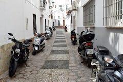 Nerja, narrow streat and motorbikes. Charming narrow street with motorbikes parked along it Royalty Free Stock Image
