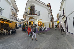 Nerja, Spain. NERJA, MALAGA, SPAIN - APRIL 17, 2013:  People strolling at sunset along the pedestrian area full by entertainment facilities in Nerja, Malaga Royalty Free Stock Photography
