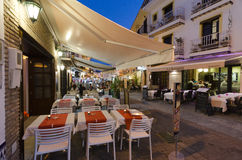 Nerja, Spain. NERJA, MALAGA, SPAIN - APRIL 18, 2013:  People strolling at sunset along the pedestrian area full by entertainment facilities in Nerja, Malaga Stock Photos