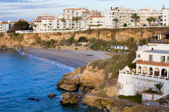 Nerja Town on Costa del Sol. Small tranquil beach surrounded by cliffs and apartment buildings in scenic resort town of Nerja at Costa del Sol, Andalucia stock images