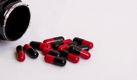 Nero-rosso, medicinale, tiro della pillola dalla scatola su fondo bianco Fotografia Stock Libera da Diritti