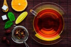 Nero-tè con gli ingredienti del tè immagini stock