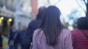 Nervöser junger weiblicher Verbrecher, der auf gedrängte Straße geht und sich herum dreht stock video
