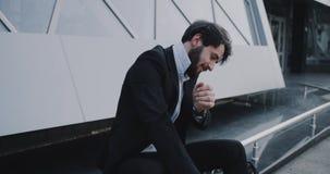 Nervös Geschäftsmann nach dem Interview, das sich neben dem Geschäftsgebäude hinsetzt stock video footage