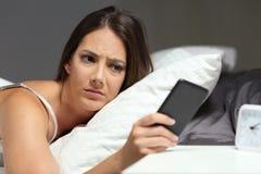 Nervös kvinna som kontrollerar telefonen i natten arkivbild