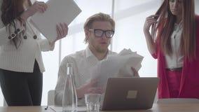 Nervös man som sitter i ett bekvämt kontor med netbook på de undersökande dokumenten för tabell som två kvinnliga kollegor stock video
