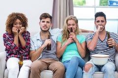 Nervösa mång--person som tillhör en etnisk minoritet vänner som hemma håller ögonen på TV royaltyfri foto