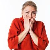 Nervöse junge blonde Frau, die ihr Gesicht für Sorge und Furcht versteckt Stockbild