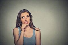 Nervöse schauende junge Frau, die ihre Fingernägel beißt stockfoto