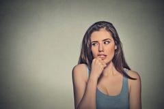 Nervöse schauende junge Frau, die ihre Fingernägel beißt lizenzfreie stockfotos
