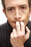 Nervöser Mann, der seine Nägel beißt Stockfotografie