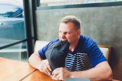 Nervöser Mann sitzt in einem Café, das auf einen Auftrag wartet lizenzfreie stockfotos